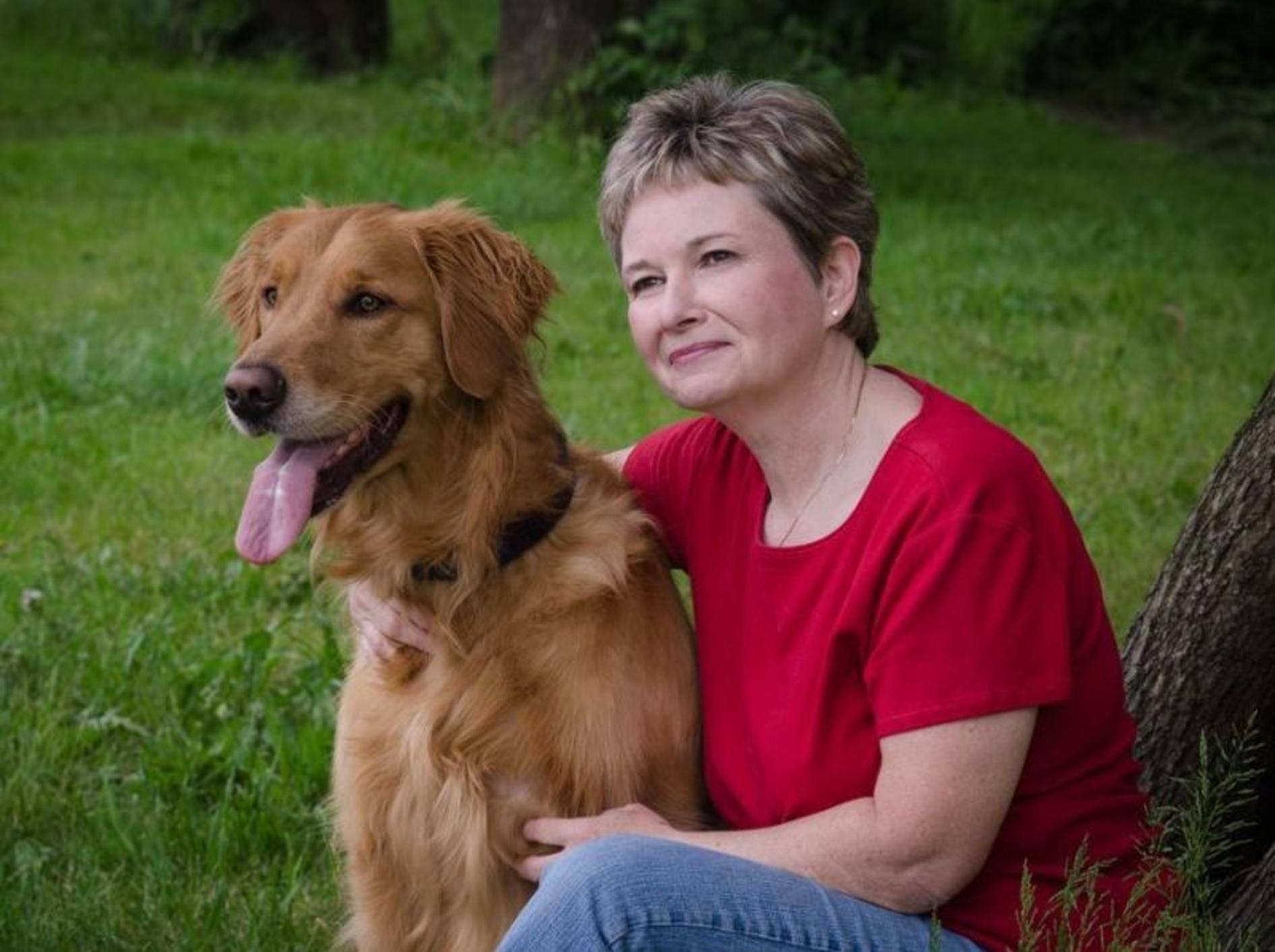Frau mit Retriever Hund auf der Wiese