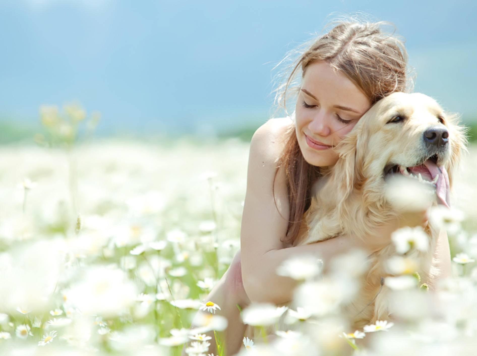 Die junge Frau genießt die Umarmung, der Hund jedoch nicht – Shutterstock / Nina Buday